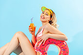 Portrait of beautiful happy woman in bathing suit sitting sexy and smiling to camera, holding rubber ring, fresh juice or cocktail, enjoying rest on summer beach