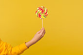 Closeup of hand holding appetizing round rainbow candy on stick, big lollipop in arm, confectionery