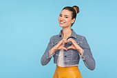 I love you! Portrait of amorous cheerful fashionably dressed woman with hair bun showing heart shape with hands