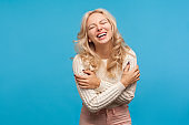 Positive optimistic woman with blond curly hair hysterically laughing enjoying life and freedom, carefree female