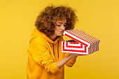 Portrait of upset displeased curly-haired woman in hoodie looking into gift box, opening present