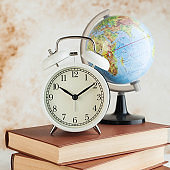 Alarm clock and globe on books. The concept of starting school, travel time.