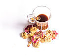 A glass cup og coffee with dried tea rose flowers around on a white background