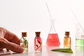 Hands preparing bottles with essence of plants in laboratory