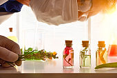 Chemist looking at bottles with essence of plants in laboratory