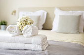 Set of clean white towels on bed