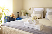 Holiday hotel room with suitcases and clean towel service