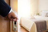 Hand in suit and shirt opening bedroom door