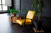 Brutal modern interior in a dark color with a yellow leather chair. Loft style living room