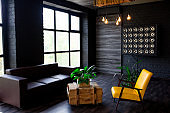 Brutal modern interior in a dark color with a leather sofa and large window. Loft style living room