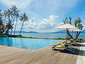 Beautiful tropical swimming pool in hotel or resort with umbrella, coconuts tree sun-loungers, palm trees with infinity pool view, ocean and mountain background.