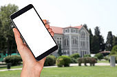 student holding smart phone in front of school