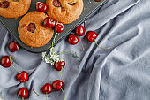 Cherry muffins with the addition of fresh cherries on on a cooling tray, close-up. Delicious dessert