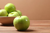 juicy green apples on a wooden table.