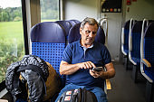 Tourist using phone while traveling by passenger train