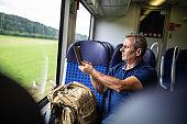 Tourist taking photos of nature through window of train