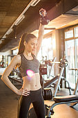 Attractive young woman holding kettlebell over her shoulders during weight training in the gym.