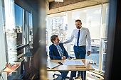 Two successful businessmen having a pleasant conversation in office
