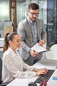 Handsome businessman working with young female secretary in office.