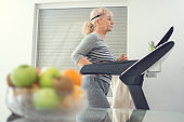 Active senior woman in sportswear jogging on treadmill at home. Home workout, active seniors, stay at home concept.