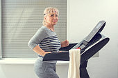 Beautiful active senior woman in sportswear running on treadmill at home. Home workout, active seniors, stay at home concept.
