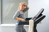 Exhausted senior woman running on treadmill at home. Active seniors and home workout concept.