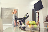 Active senior woman in sportswear walking on treadmill and watching tv at home.