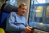 Tourist using phone and smiling while traveling by passenger train