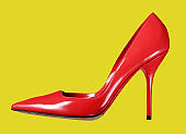 Single red leather ladies court shoe on yellow background
