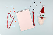 Christmas composition, wish list concept. Notebook with pen, Santa Claus