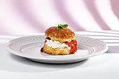 Assortment of homemade scones with ham, cheese, avocado, salmon, cream cheese and strawberry jam