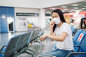 Asian tourist feeling sick, coughing ,wearing mask and sit on chair with social distancing to prevent pandemic during travel at airport terminal. new normal after coronavirus, covid-19 virus epidemic