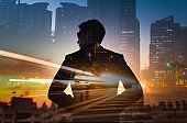 Strong, powerful, successful and determined business man standing in futuristic modern city setting. Double exposure