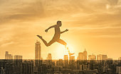 Happy fit young man jumping leaping over city buildings. Freedom,