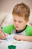 Portrait of cute kid boy drawing at the table at home. Child making craft. Education, creativity and early learning.