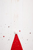 Top view of Santa's red hat is lying on a white wooden table. Shining silver and red stars are scattered on the surface like snow. New year, Christmas, holiday concept
