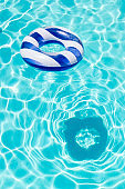 Striped Float Ring on the Surface of Crystal Clear Blue Water with Reflecting Sunlight and Shadow