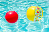 Bright Yellow Flower Beachball and Red Ball on the Surface of Crystal Clear Blue Water with Reflecting Sunlight