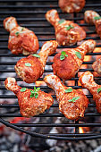 Raw and spicy chicken legs with spices on grill