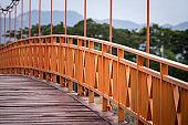 Orange steel structure suspension bridge.