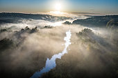 Aerial view of stunning mist over autumn river at sunrise
