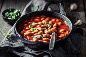 Baked beans with herbs and tomato sauce in iron dish