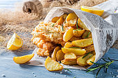 Fish cod with chips and lemon in newspaper
