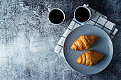 Fresh croissants on a plate with cups of coffee