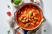 Top view of baked beans made of tomatoes and herbs