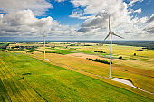 Aerial view of wind turbines on green field in Poland