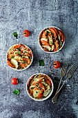 Zucchini tomato casserole with pepper and parsley in white bowl