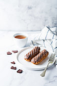Fresh eclairs on a plate with chocolate glaze