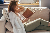 Woman resting at home and reading book
