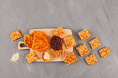 Healthy bites. Sweets made from dried fruits (dried persimmons and apricots) with nuts or sesame seeds. Grey background. Top view. Place for text